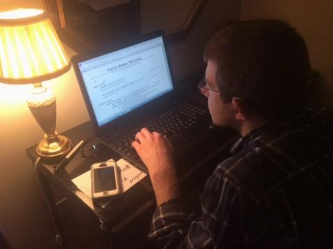 A young adult works on his resume on a computer