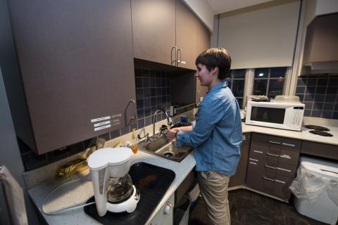 a young woman standing at a sink in a kitchen doing dishes