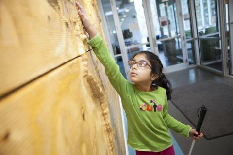 A girl with a white cane touching a tactile map