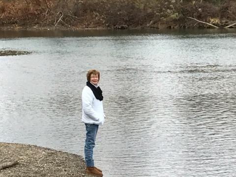 Woman standing by side of river