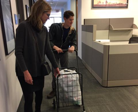 A young adult pushes a cart full of cans for recycling
