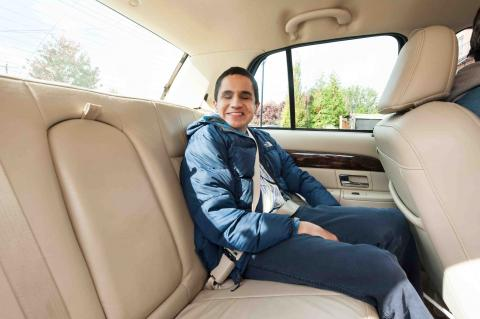 A young man who is blind sitting in the back seat of a car
