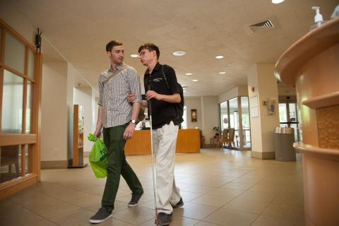 A young adult walks sighted guide through a lobby.