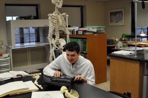 student using braille notetaker with skeleton in background