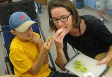Photo of Megan Mogan eating kiwi with her student.