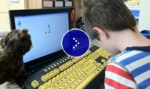 A young student sits in front of a computer with large yellow keyboard.