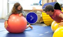 Middleschool girl with glasses and coach on balance balls.