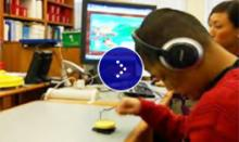 A student pressing on a yellow button and listening on the headphone.