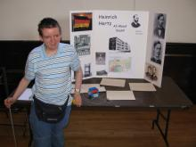 student stands in front of his project at a science fair