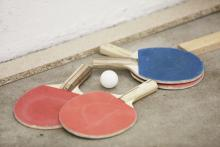 Two sets of ping pong paddles and a ping pong ball