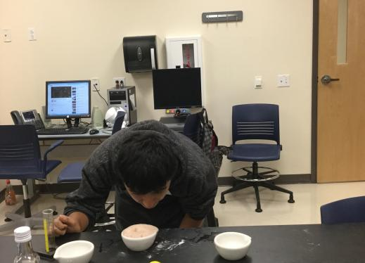 Student adding balsamic vinegar in his experiment.