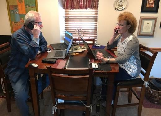 Two adults sitting at the kitchen table with their laptops open
