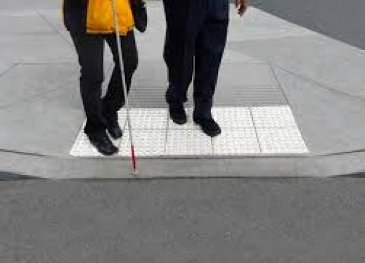 The image is of 2 people walking, one using a white cane.