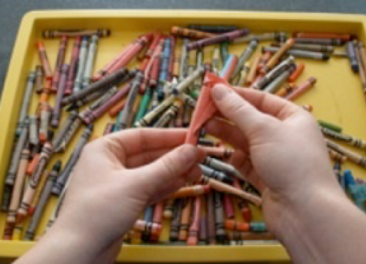 hands peeling away the wrapping of a crayon