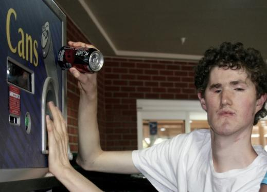 A young man who is deafblind places a can in a machine to recycle it.