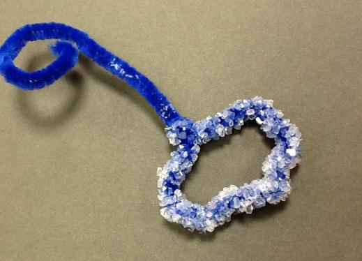 a blue heart shaped ornament made from a pipe cleaner is covered in small shiny crystals