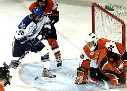 a hockey player shooting the puck, the goalie is front of the net