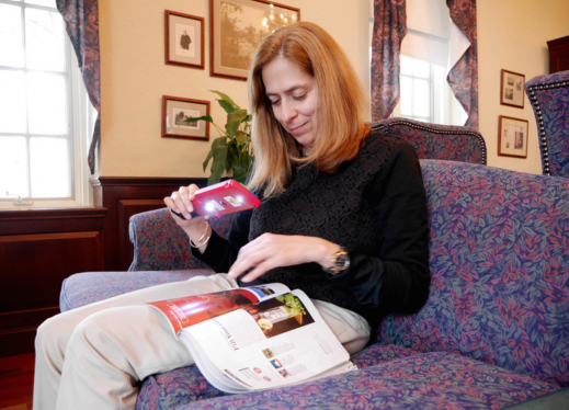 A woman sitting on a couch uses a magnifier