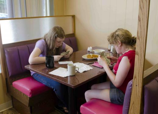 Two students count their money in a restaurant