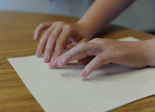 Two hands reading braille text on a piece of paper