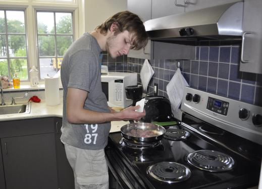 Young man cooking on stove