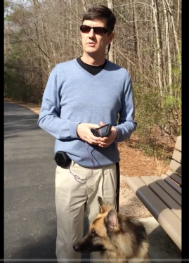 Ed Summers standing at a greenway intersection with his Seeing Eye dog, demonstrating how to set a POI using the BlindSquare app