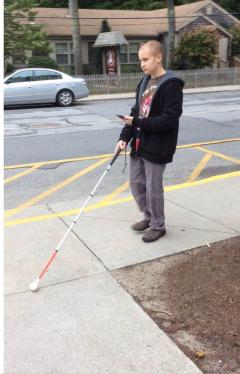 Student with long cane and iPhone standing on a sidewalk at street intersection.