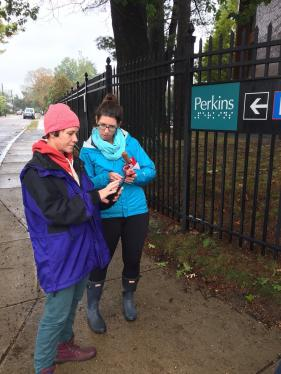 Standing in the rain by the Perkins School for the Blind fence, two O&Ms work together to learn BlindSquare.