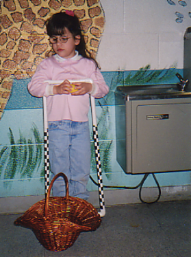 4 year old standing beside a drinking fountain in her school, opening an Easter egg; precane and easter basket are beside her.