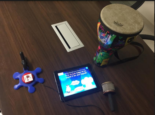 Picture of materials used with the interactive storybook: drum, musical instrument, switch, speaker, and iPad with app