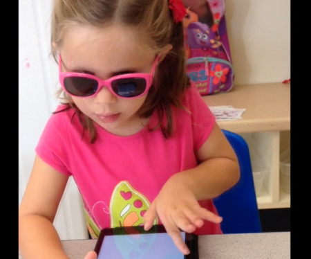 Image of an adorable four year old using an iPad with VoiceOver gestures.