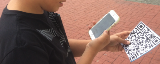 Student using an iPhone in front of a QR code.  BlindSquare on the iPhone is reading the QR code.