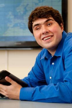 Sina Barham, a smiling man in his 20s holding a tablet.