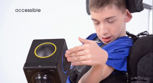 The Skoog cube is mounted on a wheelchair and a boy is pressing the side of the cube.