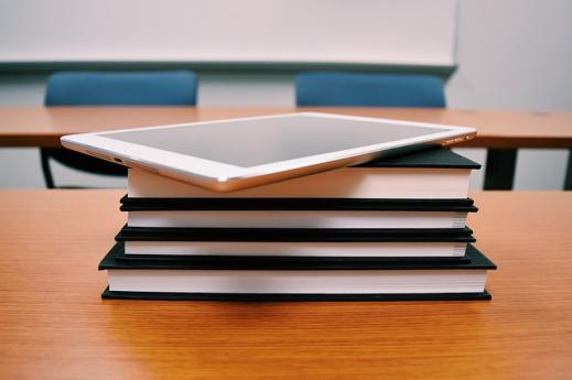 A stack of print books with an iPad on top sitting on a desk in a classroom setting.