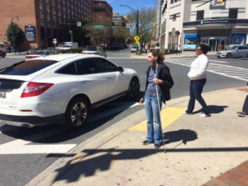 Arielle standing with her long cane at a busy city intersection.