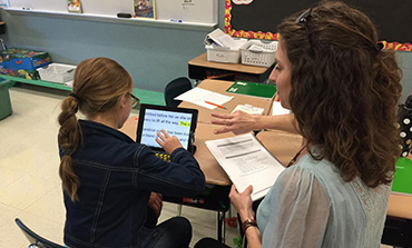 A student working on an iPad while her teacher instructs her