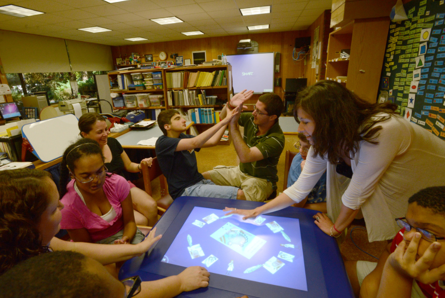 Photo of student touches a shape on a large screen.