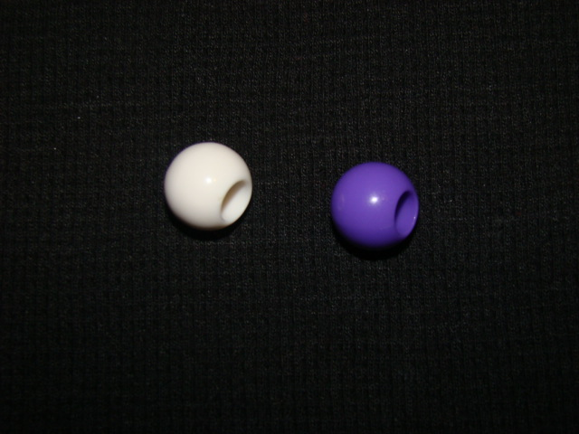 Picture of a purple and white bead representing flower color in pea plants.