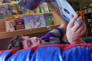 A young boy is shown reclining in a bean bag chair with a colorful illustrated book.