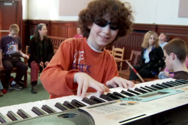 A blind boy plays an electronic keyboard in music class.