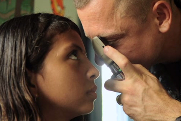 A teenage girl in Central America is getting an eye exam.