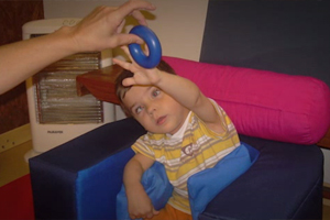 Young boy with visual impairment sits in a chair and tries to grab a blue plastic ring.