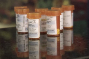A number of prescription bottles and pills are shown on a counter.