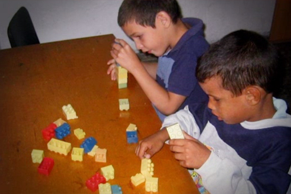 Two young boys who are blind sitting at a table in a classroom in Cuba play with Lego pieces.