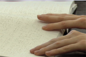 A close-up shows one boy's fingers tracking a line of braille across the page.