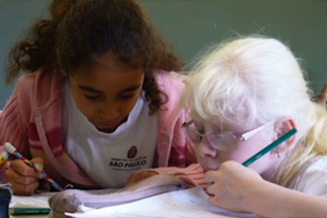 Two young girl students working closely together at a desk.