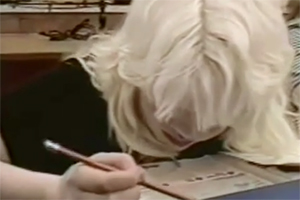 A young woman with albinism sits at a desk and reads a nonmodified worksheet.