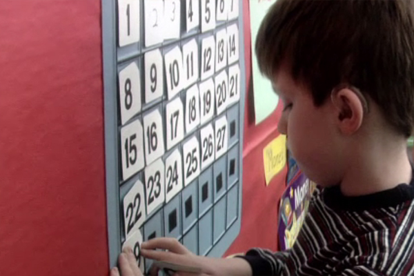 A boy place a number on the calendar grid.