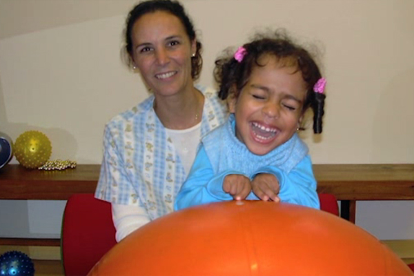 A young girl who is visually impaired and multiply disabled smiles broadly as she stands behind a large orange exercise ball.